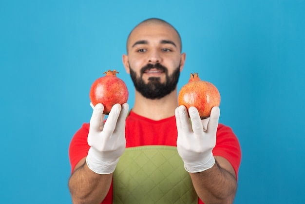 Portret van een bebaarde man in schort met twee verse granaatappels in handen.