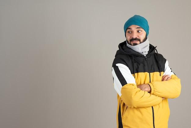 Portret van een bebaarde man in warme kleren die met gekruiste armen staat.