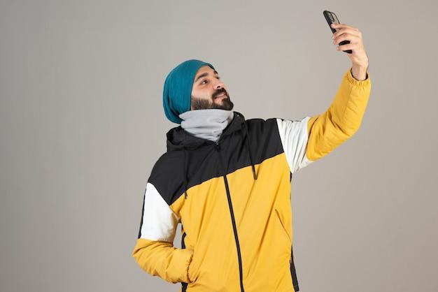 Portret van een bebaarde man in warme kleren die selfie neemt met zijn mobiele telefoon.