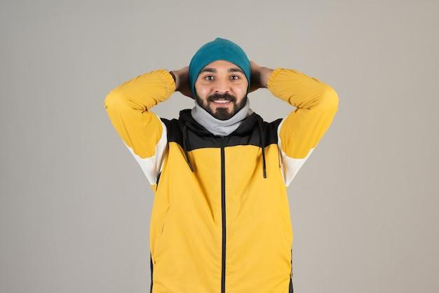 Portret van een bebaarde man in warme kleren die staat en poseert.