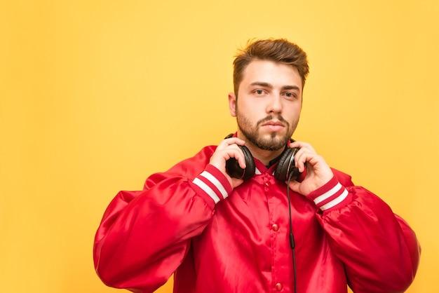 Portret van een bebaarde man in zijn koptelefoon en een rood jasje op geel