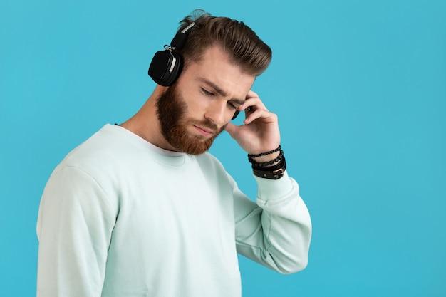 Portret van een bebaarde man, luisteren naar muziek op draadloze koptelefoon op blauw