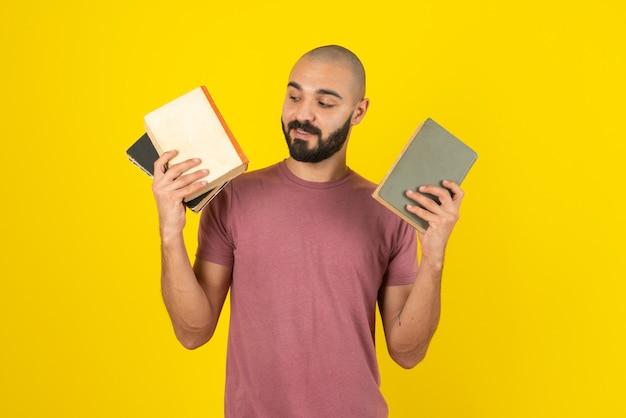 Portret van een bebaarde man met boekomslag over gele muur.