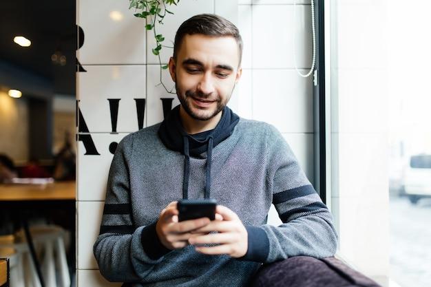 Portret van een bebaarde man met mobiele telefoon in café
