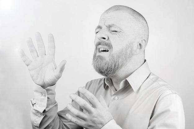 Portret van een bebaarde man met opgeheven handen met emoties op een lichte achtergrond