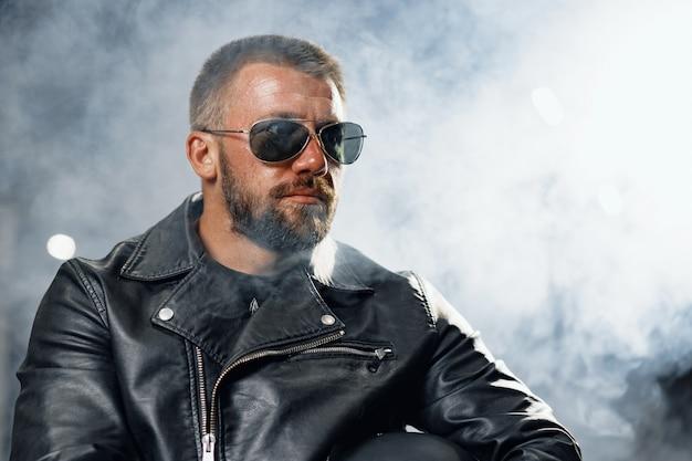 Portret van een bebaarde man motorrijder in donkere zonnebril op donkere achtergrond