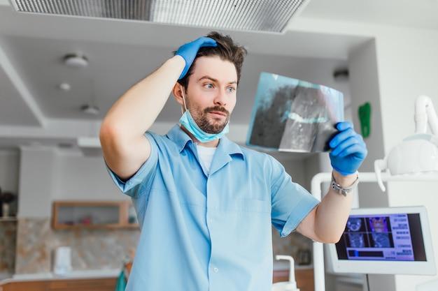 Portret van een bebaarde mannelijke arts of tandarts met een emotioneel gezicht dat naar röntgenfoto's kijkt, in zijn moderne kantoor.