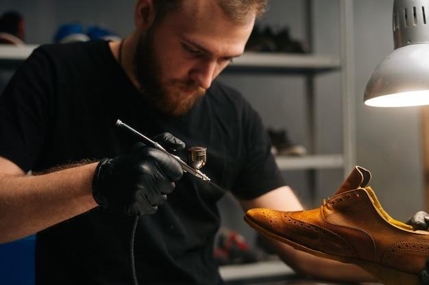 Portret van een bebaarde schoenmaker die zwarte handschoenen draagt die verf van lichtbruine leren schoenen close-up spuit