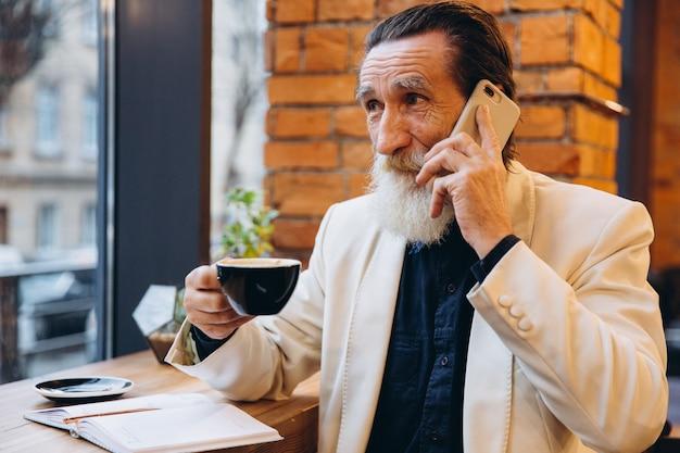 Portret van een bebaarde senior man koffie drinken en het gebruik van slimme telefoon in café. portret van gelukkig grijze bebaarde man zit in café.