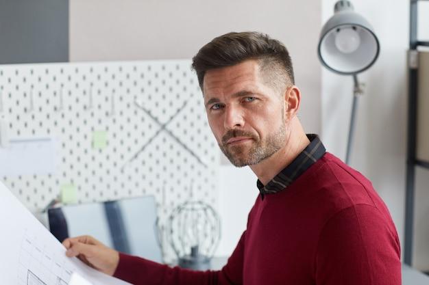 Portret van een bebaarde volwassen man met blauwdrukken en tijdens het werken in de architectuur of bouwsector,