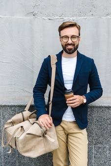 Portret van een bebaarde zakenman die een bril draagt die een papieren beker en een draagtas houdt terwijl hij in de buurt van de muur staat