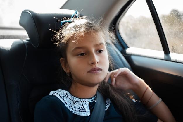 Portret van een bedachtzaam tienermeisje, zittend op de achterbank van de auto.