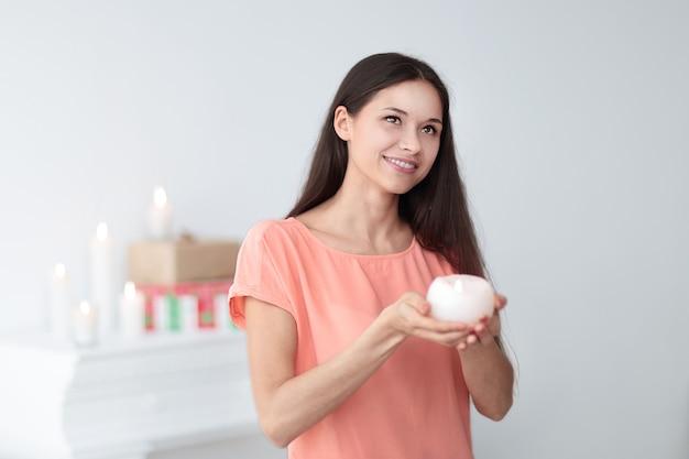 Portret van een bedachtzame jonge vrouw met een kaars