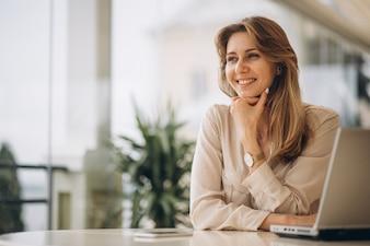Portret van een bedrijfsvrouw die aan laptop werkt