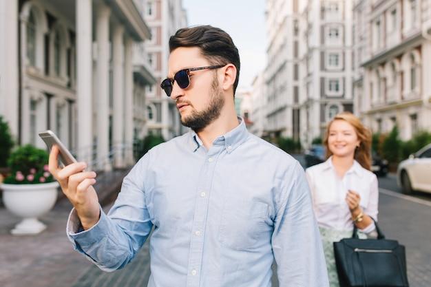Portret van een beetje triest darm in zonnebril kijken op de telefoon op straat. mooi blond meisje dat hem betrapt