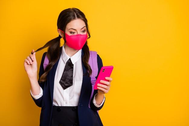 Portret van een behoorlijk flirterig schoolmeisje dat de mobiele 5g-app gebruikt