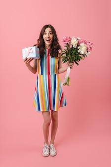 Portret van een behoorlijk verraste, geschokte, schattige vrouw die zich geïsoleerd over een roze muur bevindt met de huidige geschenkdoos en bloemen