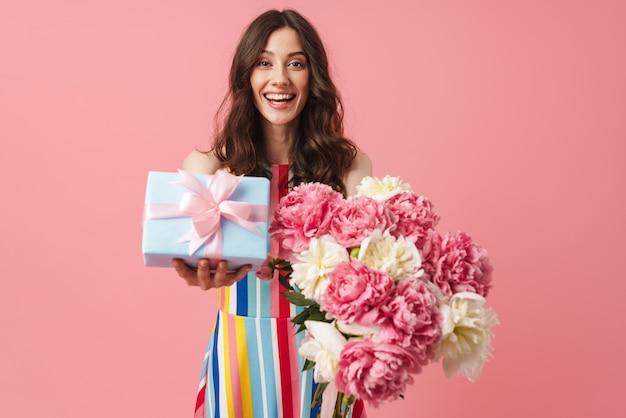 Portret van een behoorlijk verraste, positieve, schattige vrouw die zich geïsoleerd over een roze muur voordeed met de huidige geschenkdoos en bloemen