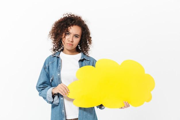 Portret van een behoorlijk verward, casual afrikaans meisje dat geïsoleerd over een witte muur staat en een tekstballon vasthoudt