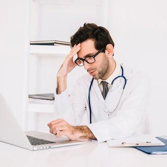 Portret van een beklemtoonde mannelijke arts die laptop in kliniek met behulp van