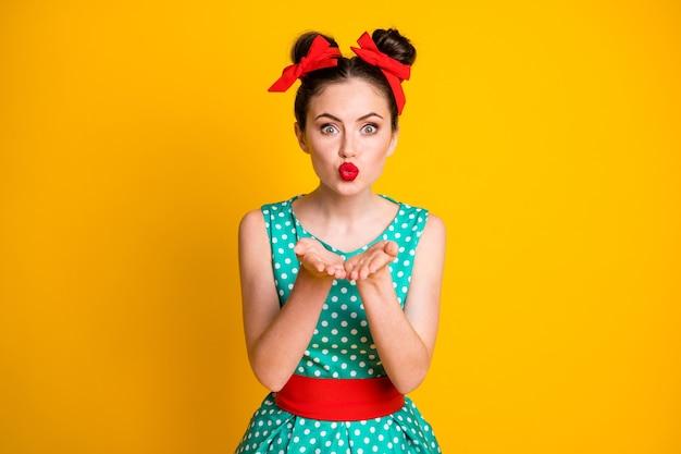 Portret van een betoverend lief meisje met een gestippelde jurk die een luchtkus stuurt die over een levendige gele kleurachtergrond wordt geïsoleerd