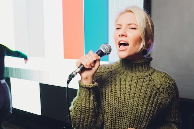 Portret van een betoverend meisje dat microfoon houdt en zingt.