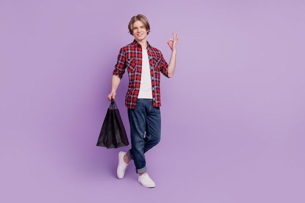 Portret van een betrouwbare shopper die koopjes vasthoudt, toont een goed gebaar op een violette achtergrond
