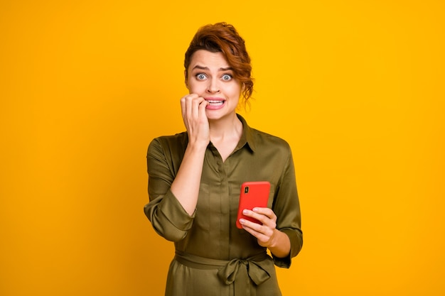 Portret van een bezorgd wanhopig meisje dat vingers van de celbijt gebruikt