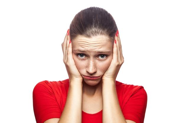 Portret van een bezorgde, bange vrouw in een rood t-shirt met sproeten die naar de camera kijkt