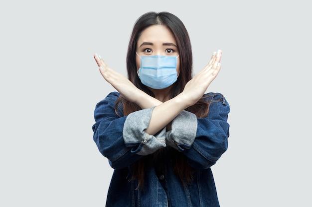 Portret van een bezorgde brunette aziatische jonge vrouw met een chirurgisch medisch masker in een casual blauw spijkerjasje dat staat en een gesloten of x-teken op de camera toont. indoor studio opname, geïsoleerd op een grijze achtergrond.