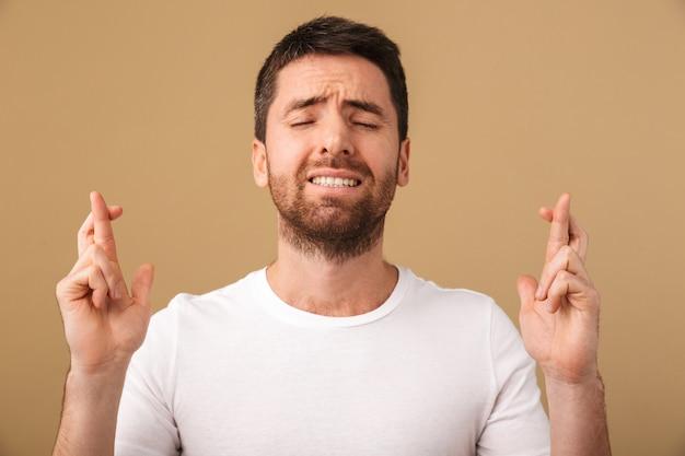 Portret van een bezorgde jonge man terloops gekleed staande geïsoleerd over beige, vingers gekruist