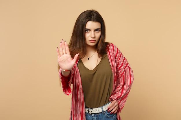 Portret van een bezorgde jonge vrouw in casual kleding die een stopgebaar toont met palm geïsoleerd op een pastelbeige muurachtergrond in de studio. mensen oprechte emoties, lifestyle concept. bespotten kopie ruimte.