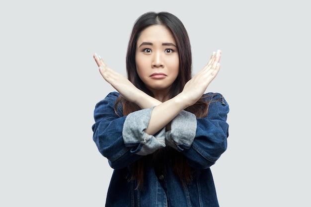 Portret van een bezorgde mooie brunette aziatische jonge vrouw in een casual blauw spijkerjasje met make-up die staat en een gesloten of x-teken op de camera toont. indoor studio opname, geïsoleerd op lichtgrijze achtergrond.