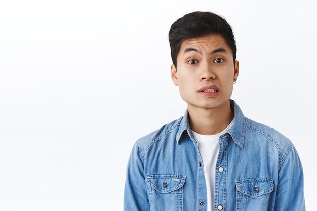 Portret van een bezorgde, onzekere jonge aziatische man die zich ongemakkelijk of twijfelachtig voelt, iets te zeggen heeft, besluiteloos kijkt, een lastige situatie ervaart, gehinderd wordt, witte muur