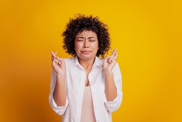 Portret van een bezorgde vrouw die met de vingers naar de lege ruimte wijst, adviseert nieuwigheid op gele achtergrond