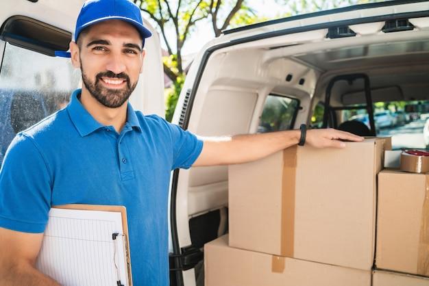 Portret van een bezorger die de producten in de checklist controleert terwijl hij naast zijn busje staat. levering en verzending concept.