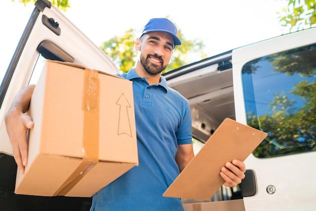 Portret van een bezorger die kartonnen dozen uit bestelwagen lost en klembordlijst controleert