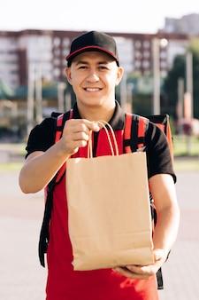 Portret van een bezorger met een rood uniform die voedselzakken vasthoudt, wachtend op de close-up van de klant, gelukkig jong