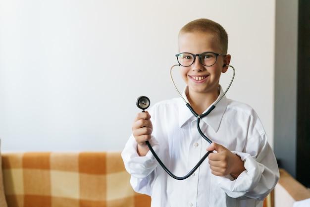 Portret van een blank mannelijk kind in een doktersgewaad met een phonendoscope in de hand en een bril speelt ...