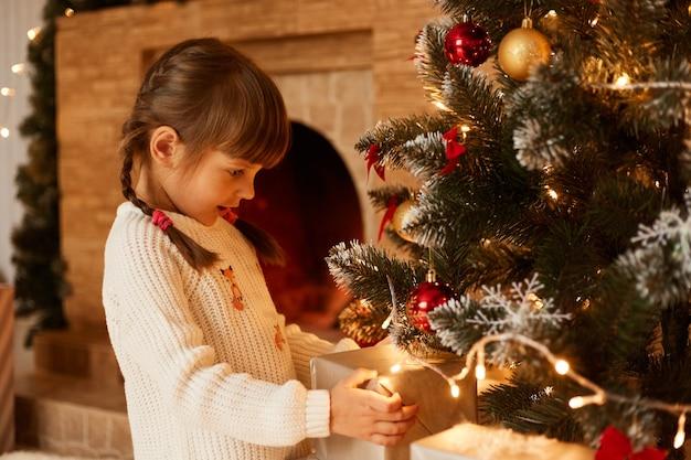 Portret van een blank meisje dat in de buurt van de kerstboom staat en dozen presenteert, een geklede witte trui, donker haar en staartjes, prettige kerstdagen en een gelukkig nieuwjaar.