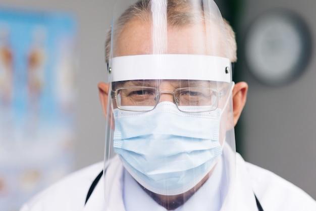 Portret van een blanke arts met een bril draagt een transparant beschermend gezichtsmasker en een overall in een ziekenhuiskamer