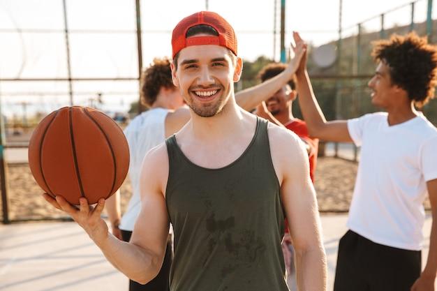 Portret van een blanke gespierde man die bal op zijn vinger draait, tijdens het spelen van basketbal op de speelplaats buiten met zijn vrienden