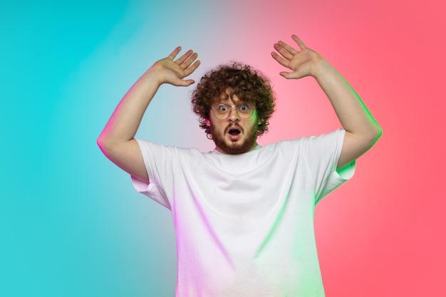 Portret van een blanke jonge man geïsoleerd op de achtergrond van de gradiëntstudio in neonlicht. mooi mannelijk model in casual stijl.