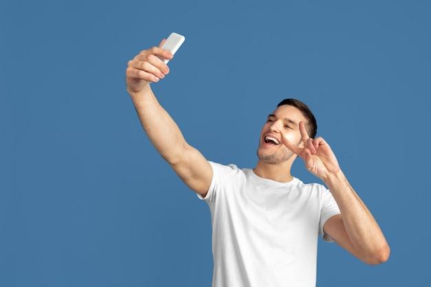 Portret van een blanke jonge man geïsoleerd op een blauwe achtergrond.