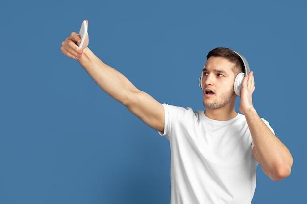Portret van een blanke jonge man op blauw