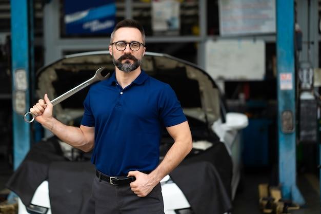 Portret van een blanke man die lacht naar de camera en grote moersleutelhulpmiddelen in de hand. expertise monteur werkzaam in auto reparatie garage.