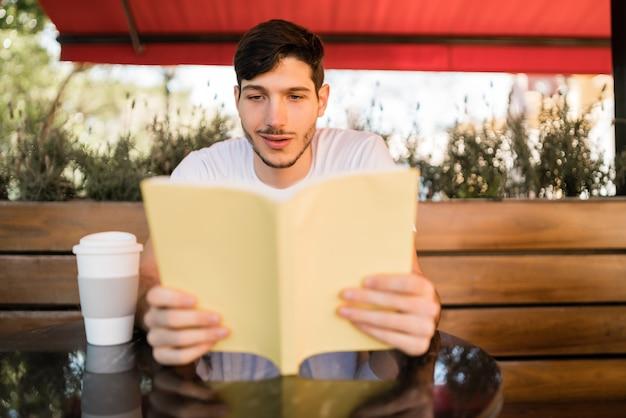Portret van een blanke man die van vrije tijd geniet en een boek leest terwijl hij buiten zit in de coffeeshop. levensstijl concept.