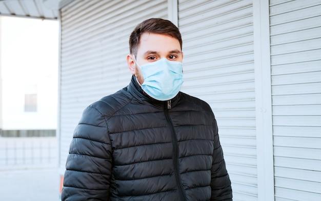 Portret van een blanke man in hygiënisch gezichtsmasker, ademhalingsbeschermingsmasker buitenshuis