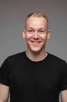 Portret van een blanke man in zwart t-shirt kijkt en glimlacht geïsoleerd op een grijze muur