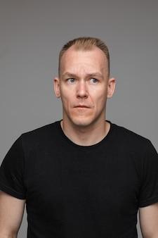Portret van een blanke man in zwart t-shirt kijkt opzij geïsoleerd op grijze muur